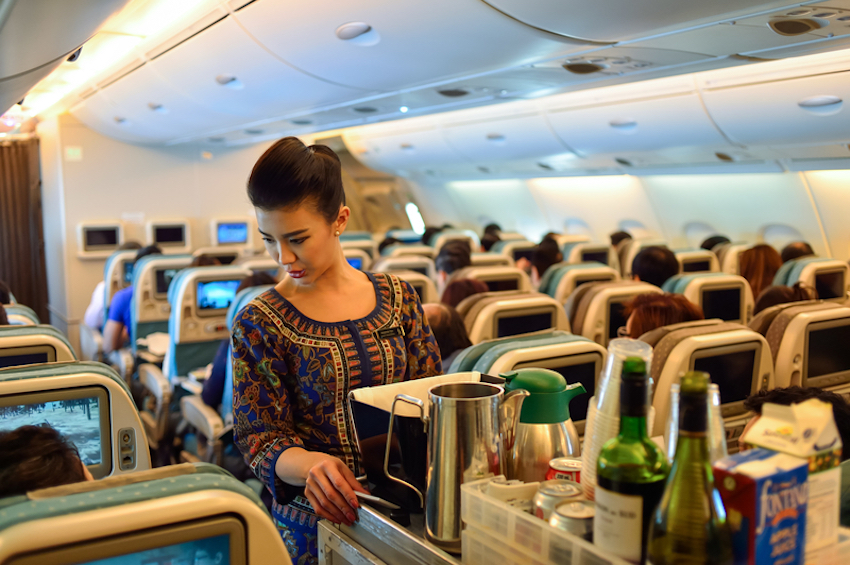 Singapore Airlines Crew serving onboard guests © Tea | Dreamstime.com